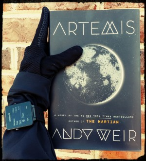"Hand wearing sports gloves and a GPS watch holding a copy of ""Artemis""."