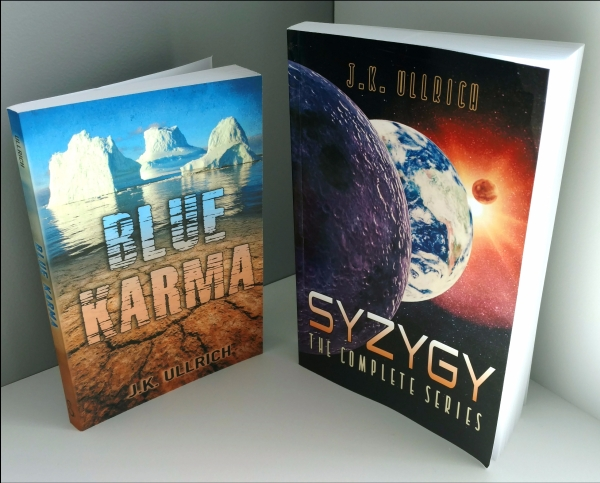 "Two paperback books, ""Blue Karma"" and ""Syzygy"""